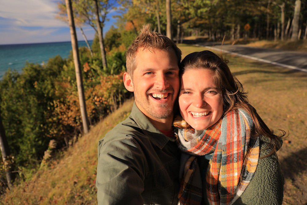 Scott and Steph from the Each Day Slow blog take a photo along Northern Michigan's scenic Tunnel of Trees in the fall.