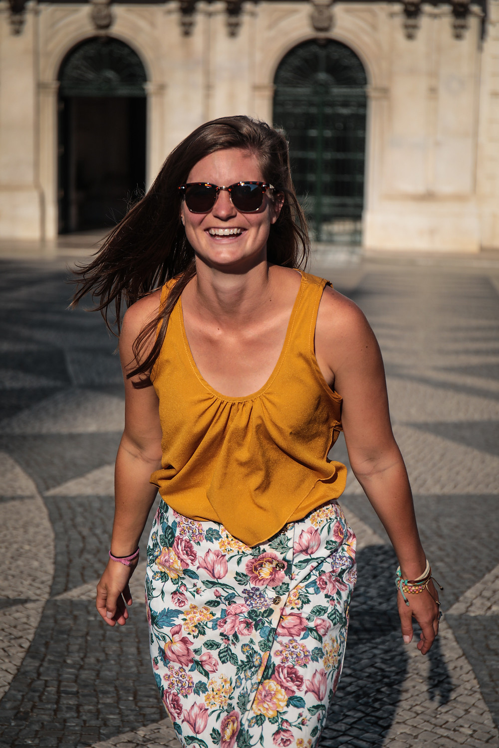 Steph Castelein from Each Day Slow laughing while traveling in Lisbon, Portugal.