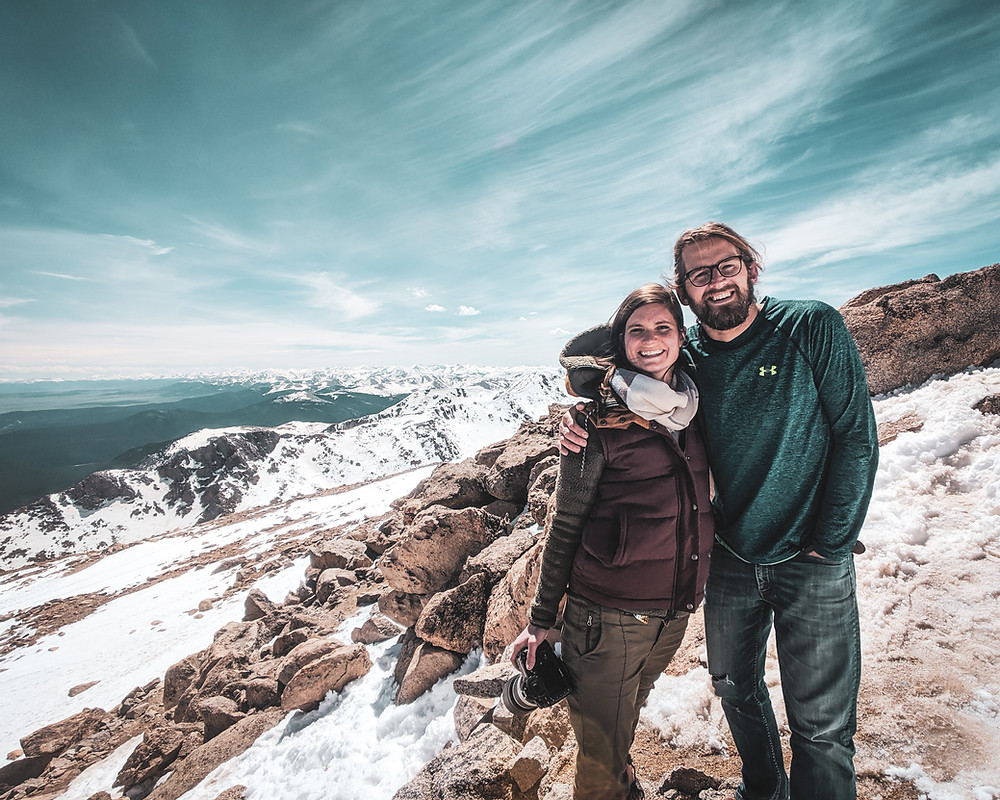 Steph and Scott from Each Day Slow take a picture at the top of Mt. Evans in Colorado celebrating one year of marriage.
