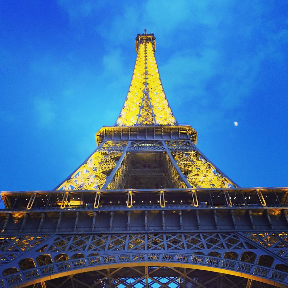 The Eiffel Tower lit up in the dark night sky.