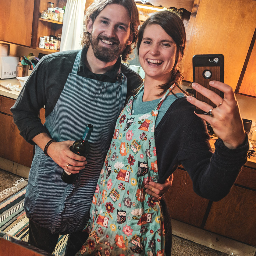 Steph and Scott from Each Day Slow in aprons while cooking in Northern Michigan.