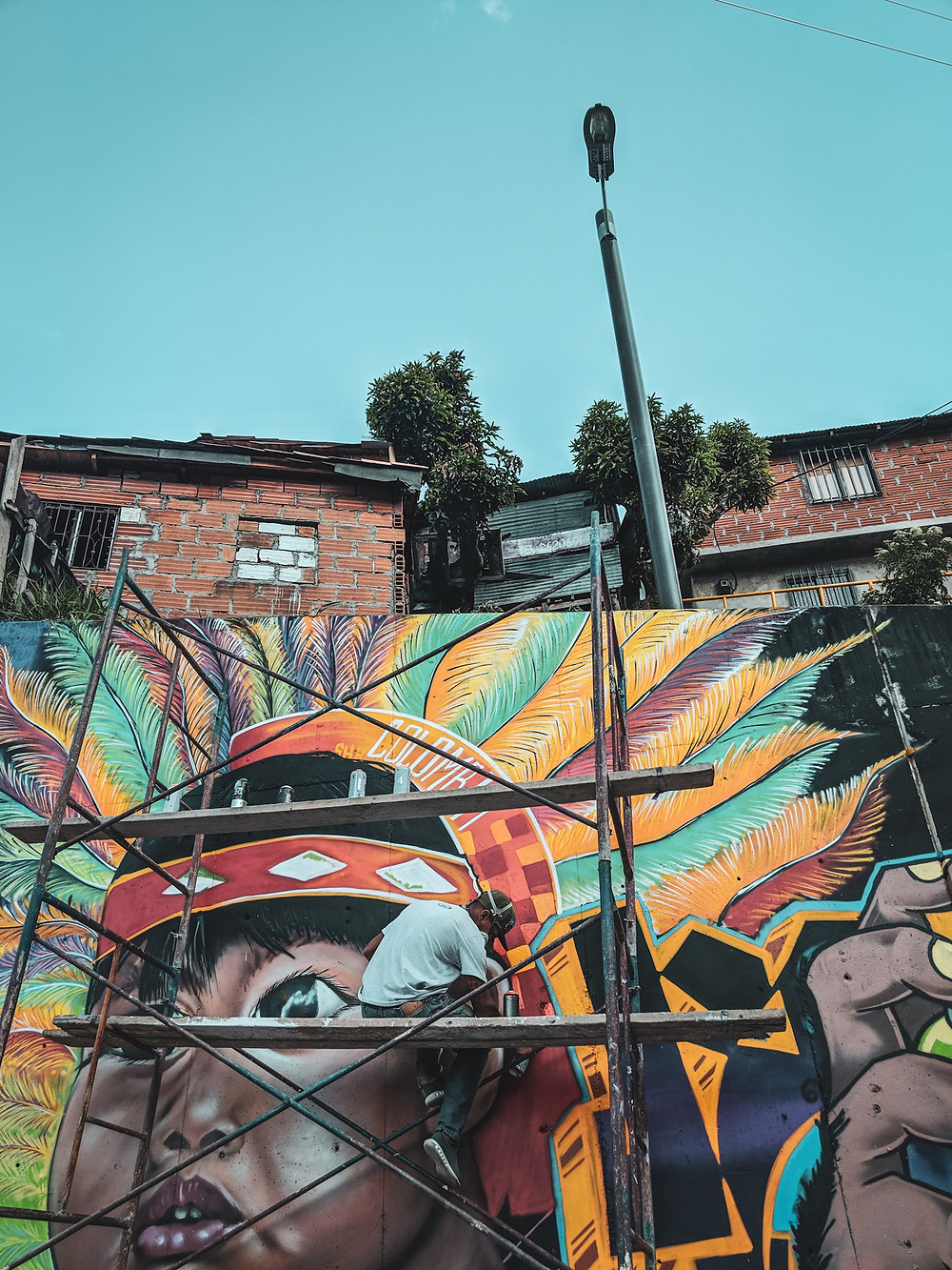 An artist creating a graffiti mural in Comuna 13 in Medellín, Colombia.