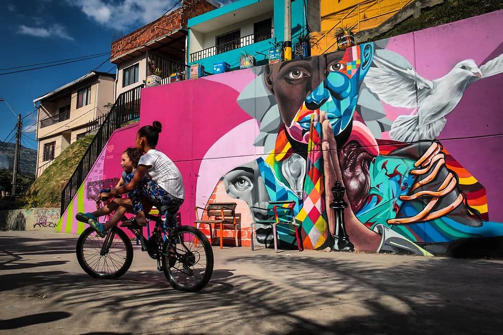 Two kids riding bikes past a graffiti mural in Comuna 13 in Medellín, Colombia.