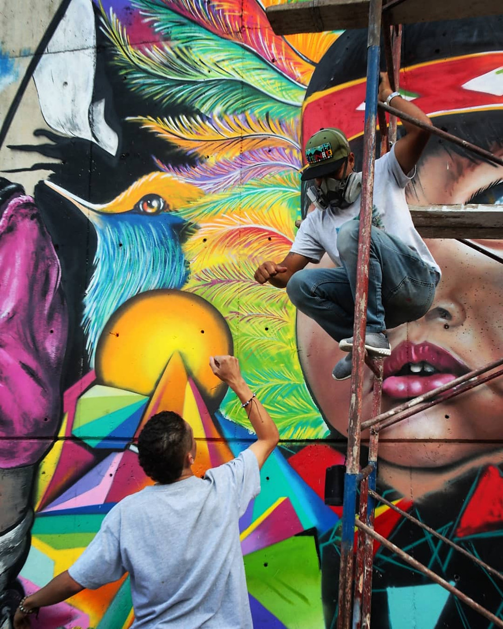 Man gives his friend a high five while creating a graffiti mural in Comuna 13 in Medellín, Colombia.