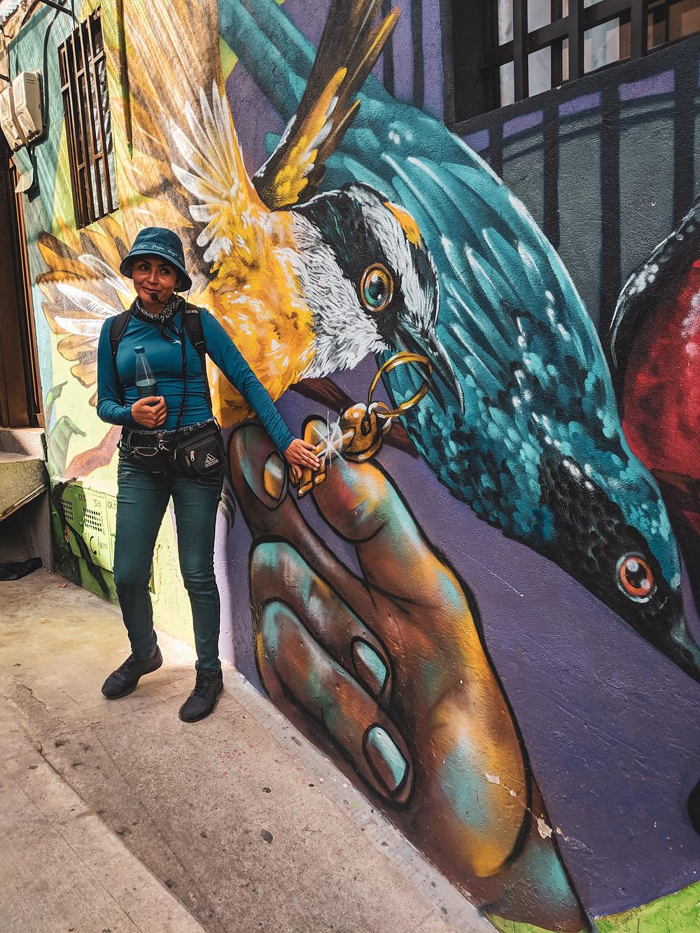 Guide explaining graffiti murals in Comuna 13 in Medellín, Colombia.