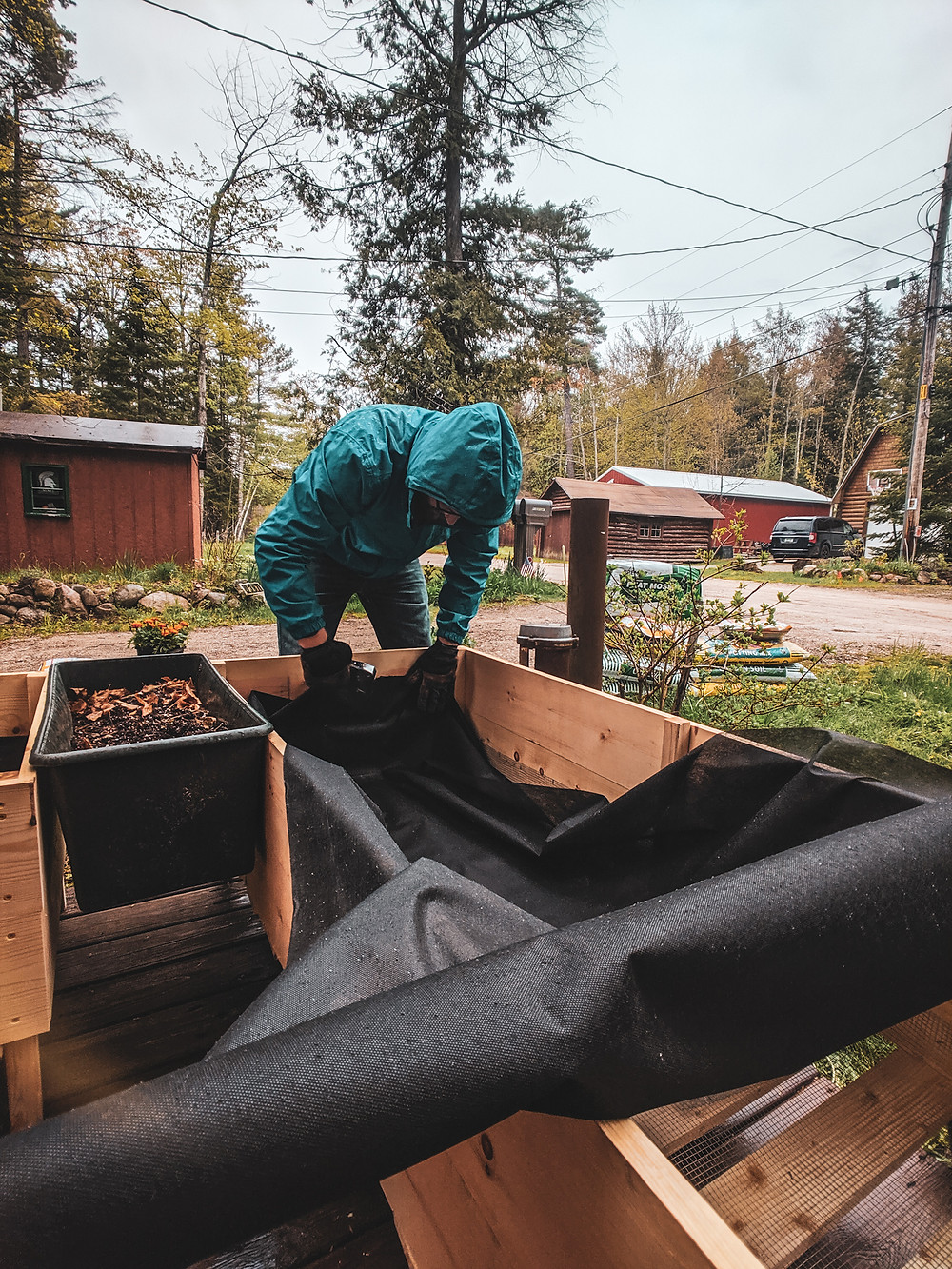 Attaching the weed control fabric to our DIY raised garden beds in Northern Michigan designed by Steph Castelein at the Each Day Slow blog.