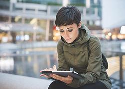 A leitura da mulher nova em Tablet