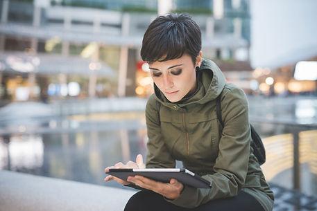 Eine junge Frau liest auf Tablet