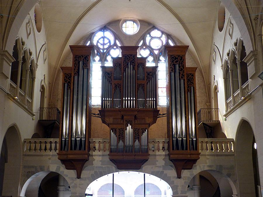 Photo du grand orgue derrière lequel on voit une partie des vitraux
