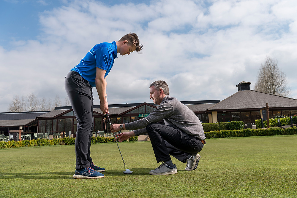 A golf coach adjust the stance and putter position of a golfer at The Vale Hotel.