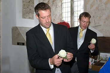 Groom grappling with his button hole