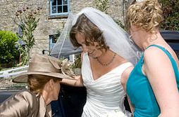 Bride adjusts her dress with Mum.