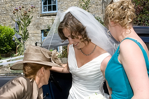 Bride adjusts her dress with Mum.