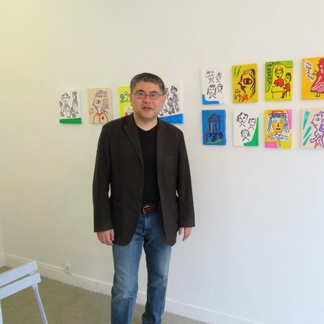 Kensuke Shimizu standing next to his artworks