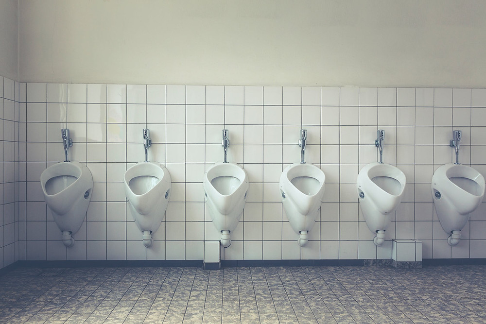 row of white urinals lined up against white tiled wall