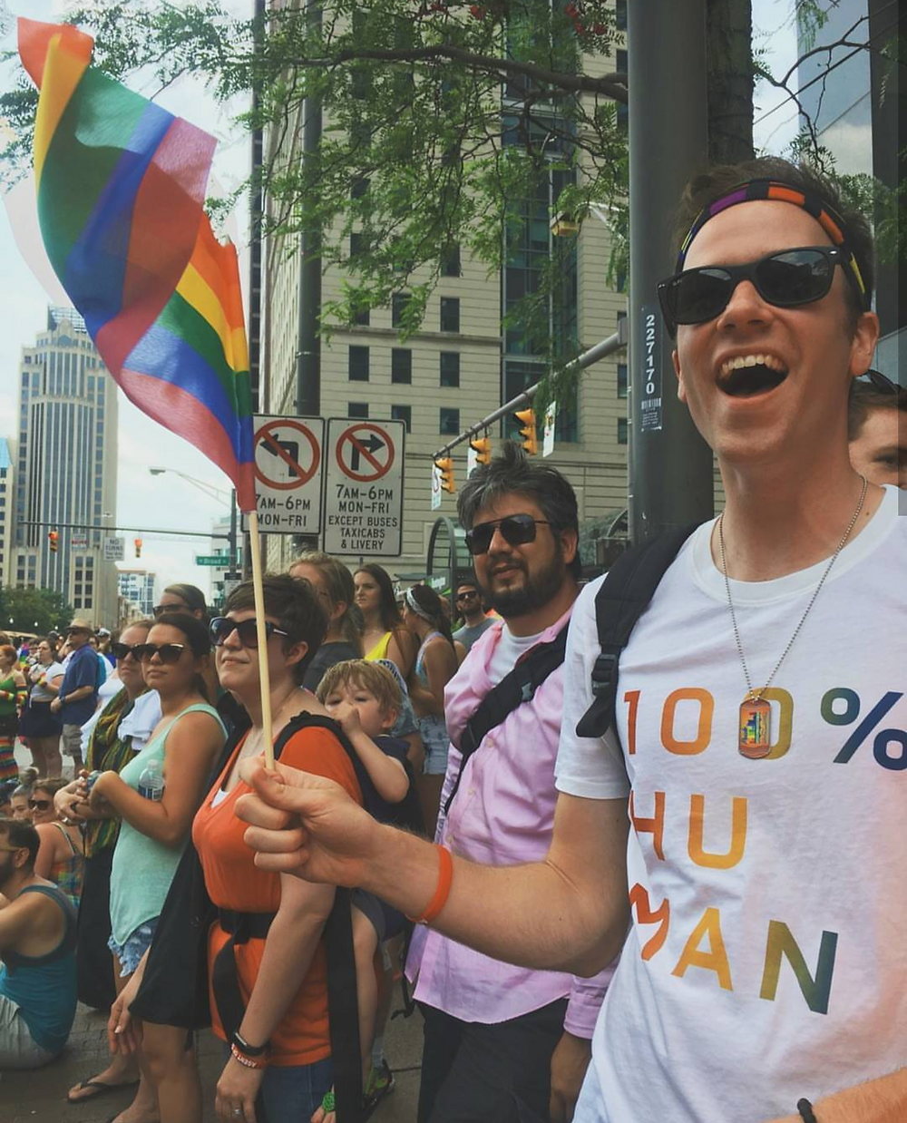 gay man with rainbow flag at lgbt pride parade