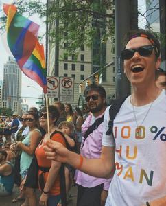 gay man with rainbow flag at lgbt pride parade