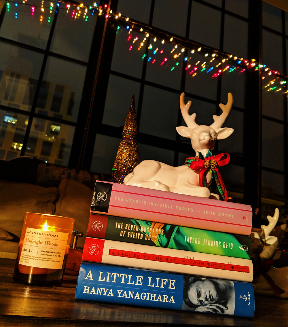 4 books in a stack by candle and christmas lights