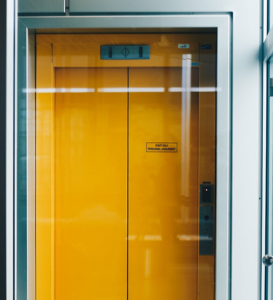yellow elevator with glass in front