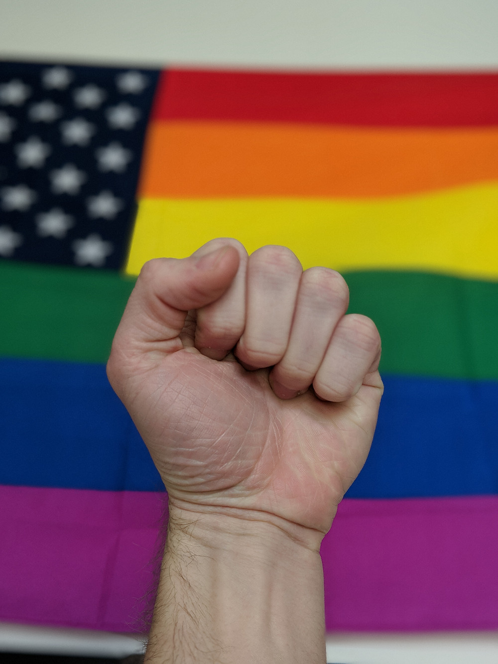 fist in front of rainbow lgbt flag