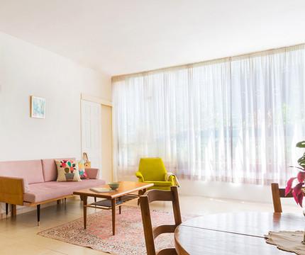 ווילון גדול שמסנן את האור ותורם לפרטיות הותקן בחלון סלון הגדול
