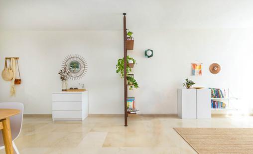 קיר הכניסה השתרע עד קצה הסלון. חצינו אותו בעזרת  הכוננית הזאת, שגם יצרה סלון יותר אינטימי וגם אפשרה מקום לתצוגה ואחסון נוח ויפה של הספרים