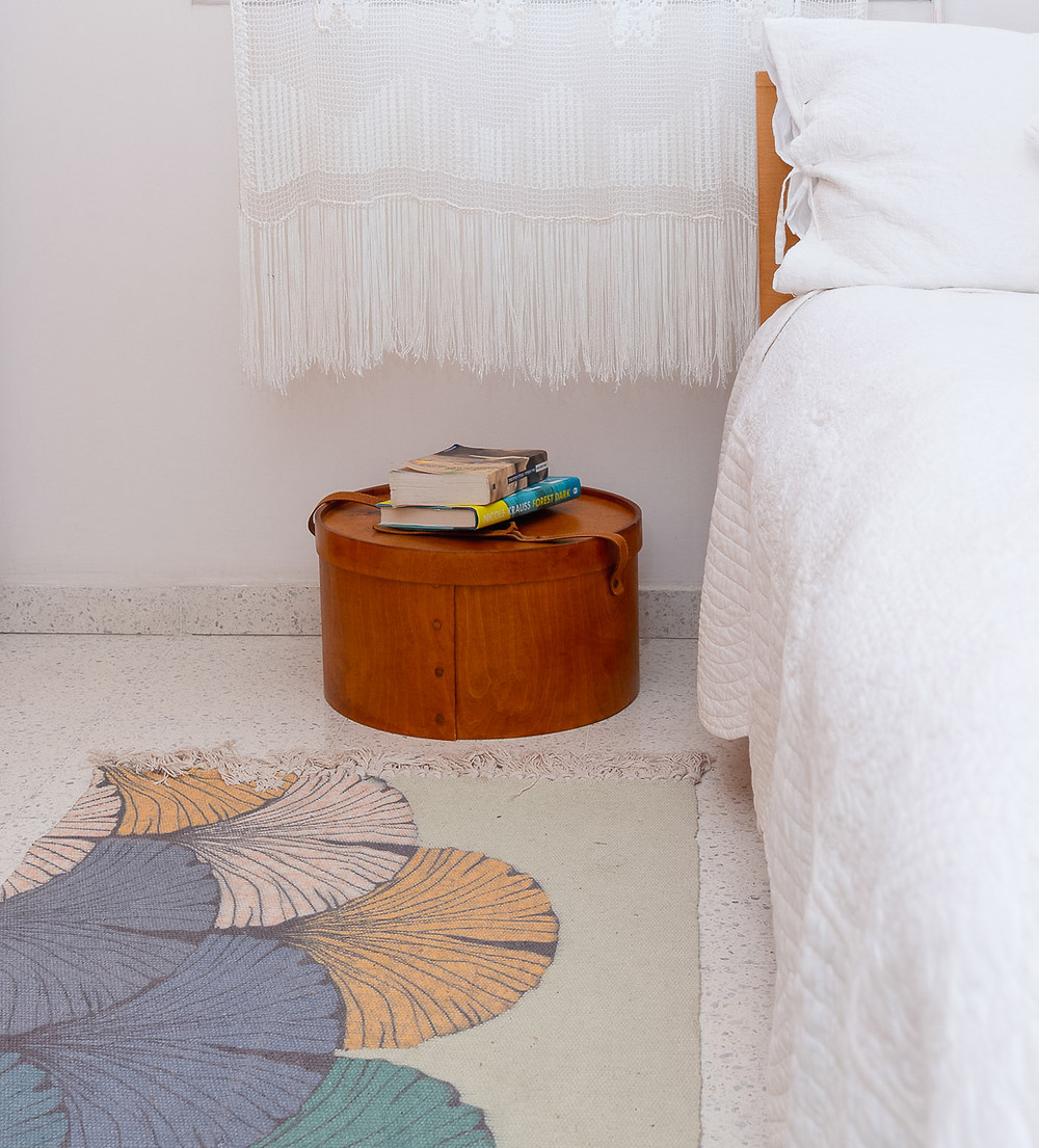 עיצוב חדר שינה סטודיו חיית וינטאג' - קופסת כובעים ישנה משמשת כשידה ליד המיט