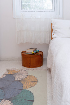 ליד המיטה - ארגז כובעים ישן מעץ קיבל את תפקיד השידה