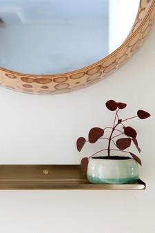 המראה הועברה לחלל הציבורי שבין חדר השינה לסלון וזכתה למדף מוזהב
