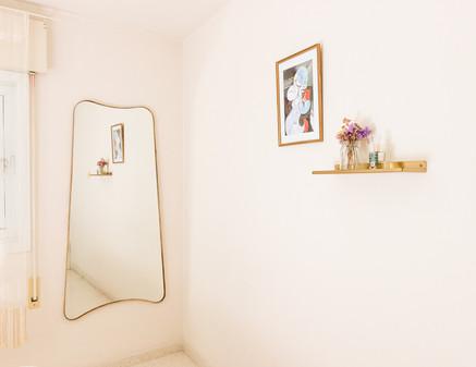 משמאל - מראת גוף בעלת צורה אמורפית ומסגרת זהובה  בקיר ליד - מדף זהוב ותמונת פיקאסו נוספת