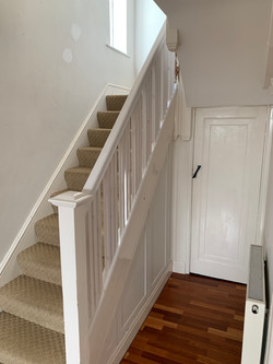 Primed handrail with primed spindles grouped in 3s