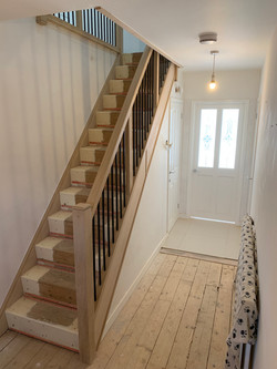 Oak cladded stair with oak handrail and black metal spindles