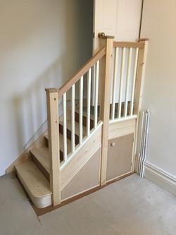 Standard stair with oak handrail and understair cupboard