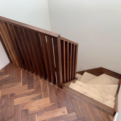 Walnut string staircase with full height walnut spindles