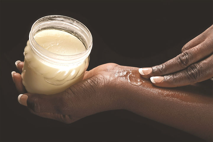 close up hands of a young black african woman smearing shea butter on black studio background_edited