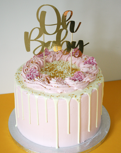 Pink baby shower drip cake with topper