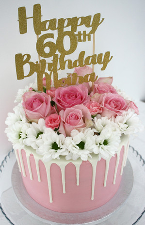 Pink buttercream cake with white chocolate drip topped with fresh flowers