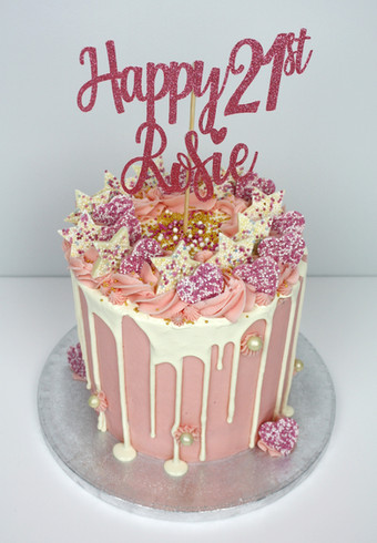Pink and white drip cake topped with chocolates and topper