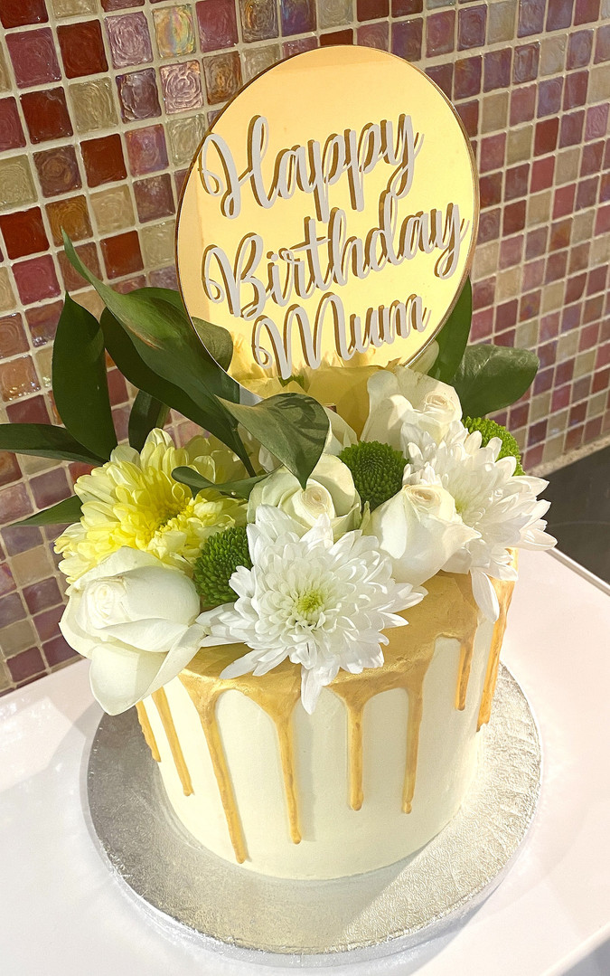 Cream and gold buttercream drip cake with fresh flowers