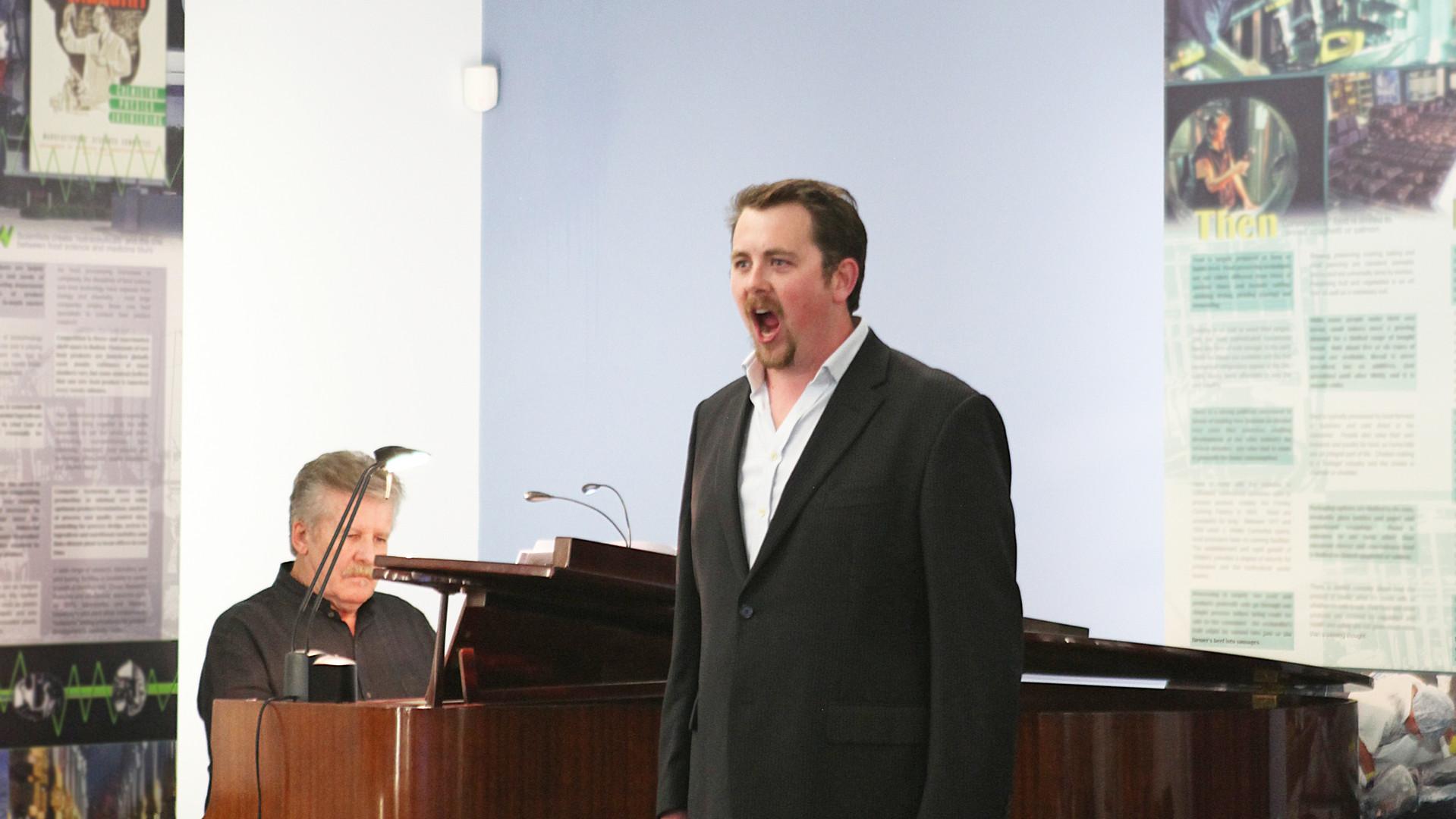 tutor robert tucker sings at school open