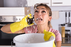 Shocked Woman Calling Plumber While Collecting Water Leaking From Ceiling Using Utensil.jp