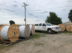 Company truck surrounded by reels of fiber optic cable