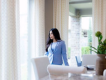 Latina woman in blue suit standing in dining room looking out the window