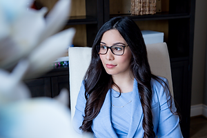 Houston woman realtor with dark rimmed glasses in a blue suit sitting at her desk for branding photoshoot