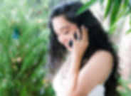 Latin woman smiling talking on the phone in a garden