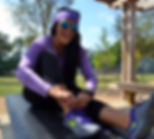 theFITista in black and purple workout gear with sunglasses tying her shoes