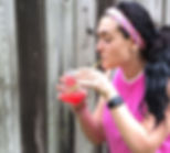 theFITista in pink workout gear sipping red juice in a glass