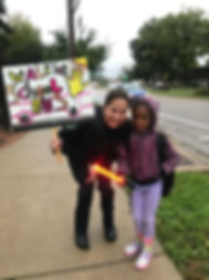 A route leader holding a Walking School Bus sign with a young student