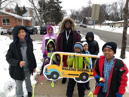 Mendota Ridgecrest Walking School Bus route leader with children holding a school bus shaped Walking School Bus sign
