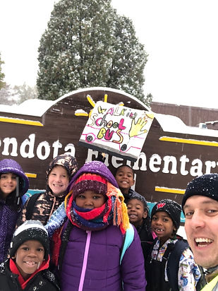 Shawn Koval with studets from Mendota Elmentary holding a Walking School Bus sign